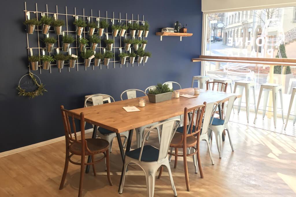 Langer Tisch mit Stühlen im Unverpacktladen ohne PlaPla