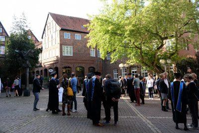 Absolvent*innen und Gäste warten vor dem Glockenhaus