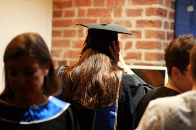 Absolventin des MBAs 2019 von hinten mit Hut