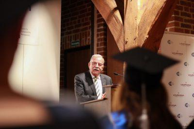 Bürgermeister Eduard Kolle aus Lüneburg gratuliert Absolvent*innen des MBAs am Rednerpult im Glockenhaus