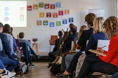 Teilnehmer*innen der Fachkonferenz hören Vortrag zu den SDGs