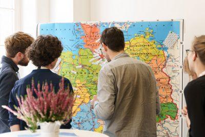 Teilnehmende der Fachkonferenz vor Deutschlandkarte mit Herkunftspfeilen